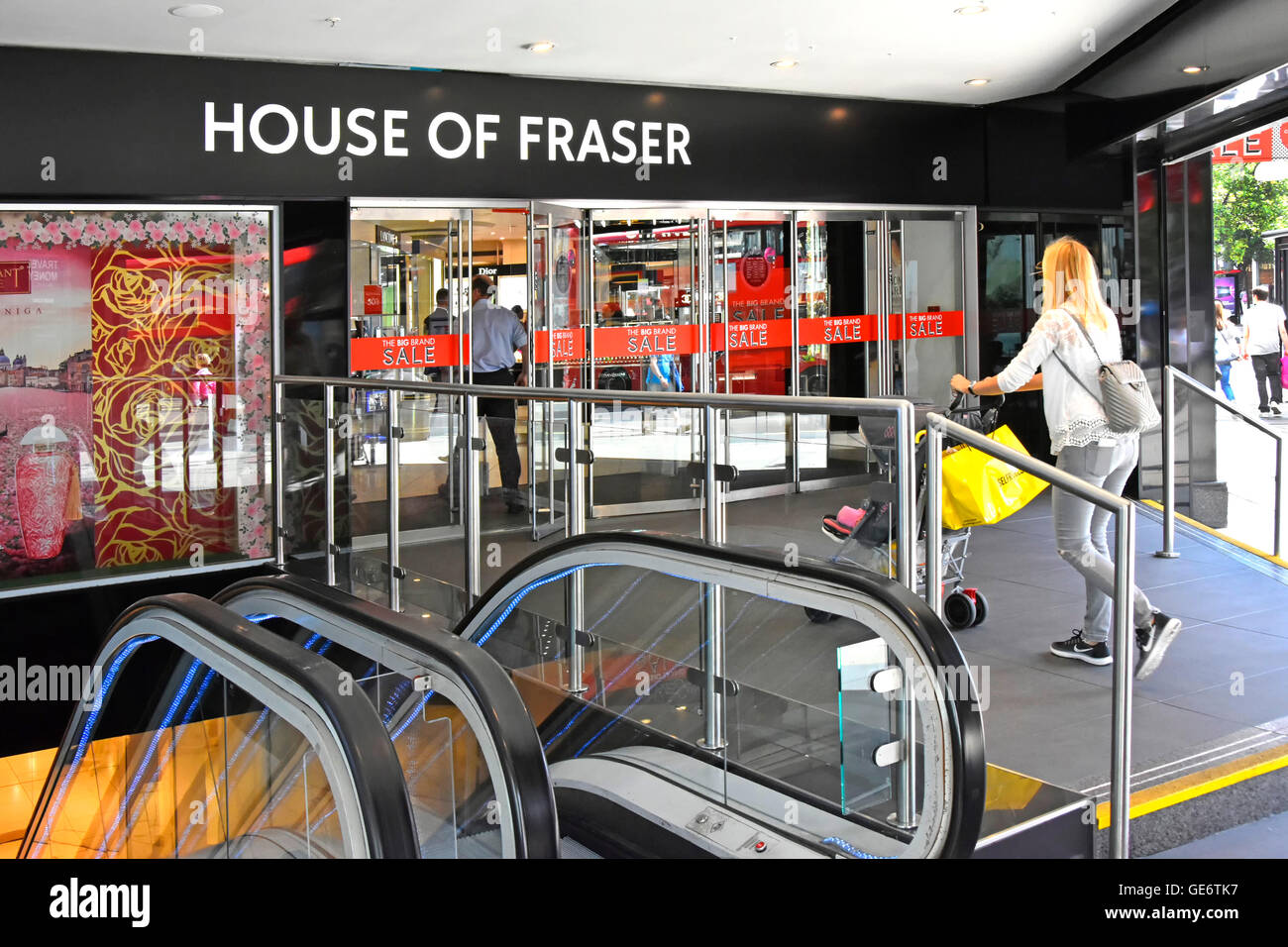 Doorway to ground floor entrance of Oxford Street branch of House of Fraser department store with escalators to - Stock Image