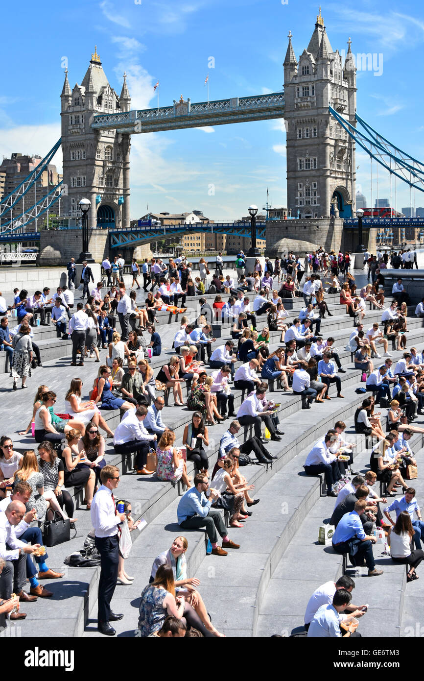 Hot day for office workers & tourists at summertime lunch break around 'The Scoop' amphitheatre London - Stock Image