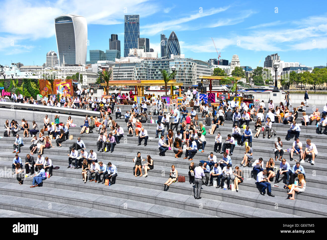 Southwark office workers taking hot sunny lunch break at the More London Scoop riverside amphitheatre with City - Stock Image
