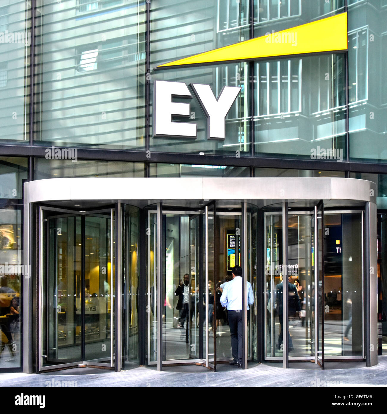 London office revolving door entrance with Ernst & Young logo & sign above for multinational professional - Stock Image