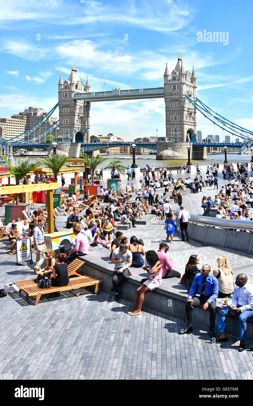Hot day for office workers & tourists at summertime drinks & food stalls around 'The Scoop' beside - Stock Image