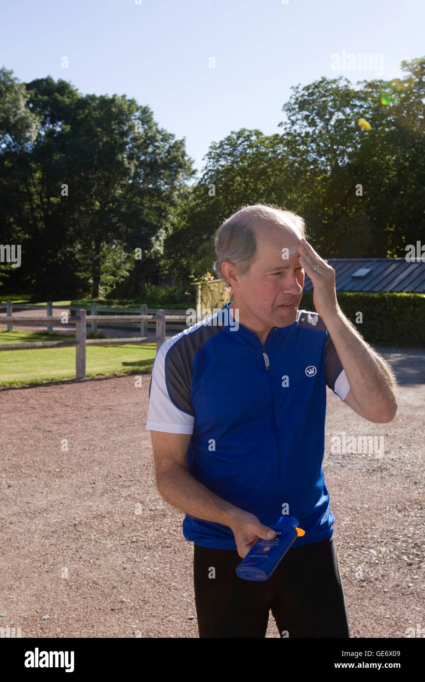 Larry Athan, participant in a Backroads cycle tour of the Loire Valley, applies sunscreen before setting off on - Stock Image