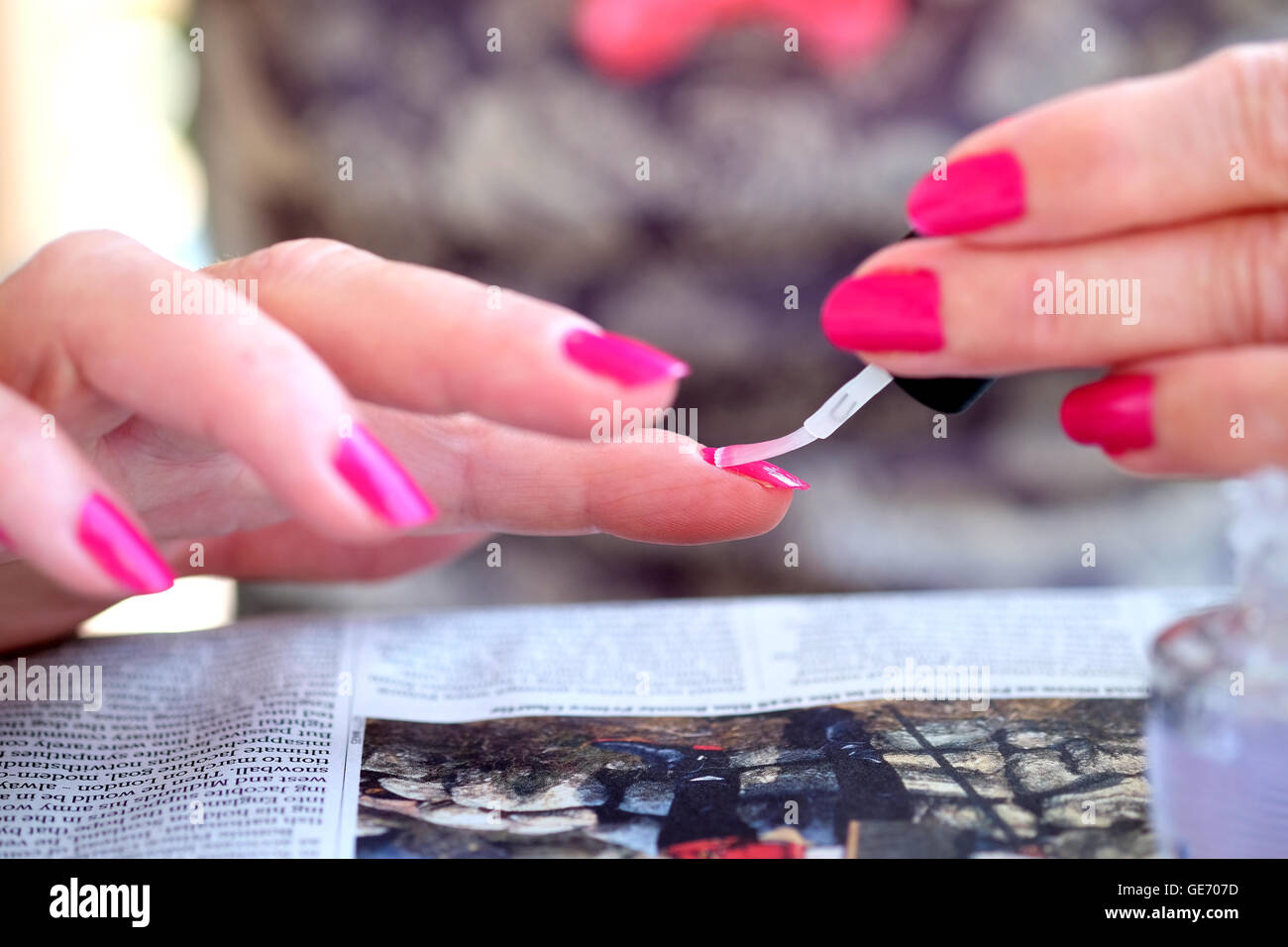 a female applying bright pink nail varnish with a brush - Stock Image