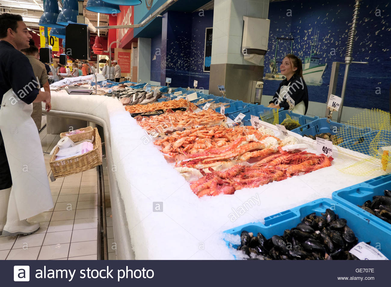 A frsh fish food counter in a French supermarket with a large display of shell fish - Stock Image