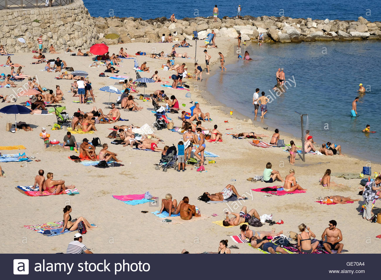 A busy beach scene on a lovely, hot sunny day in Antibes, France - Stock Image