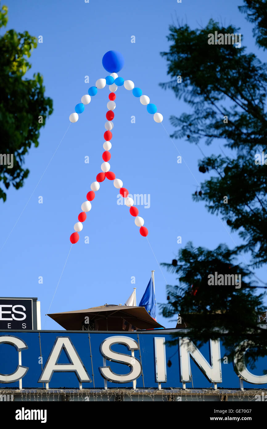 A figure made from balloons in the colors of the French flag flying above a Casino - Stock Image
