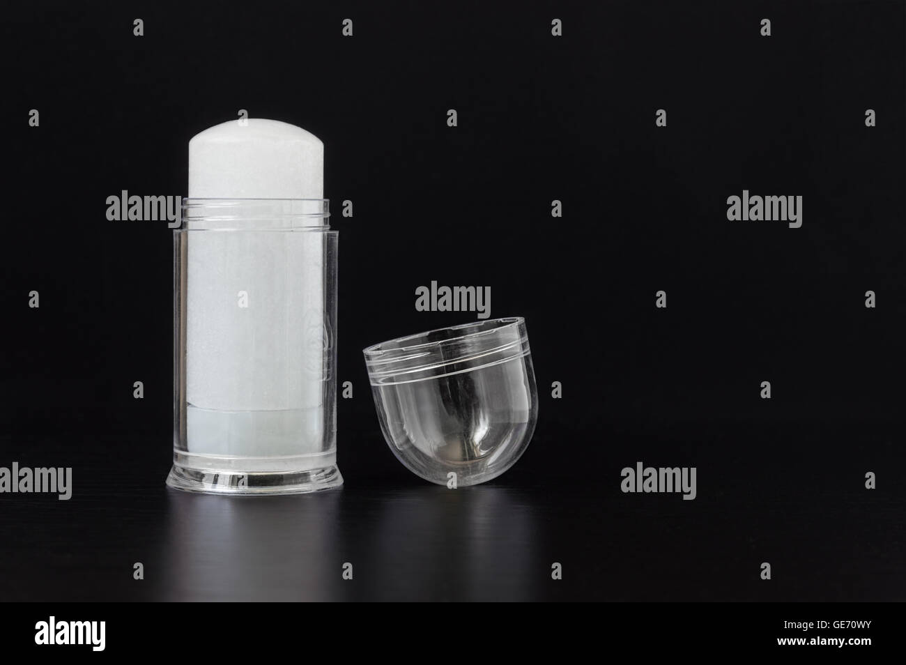 Alum crystal push-up deodorant stick in protective transparent plastic case on black background - Stock Image