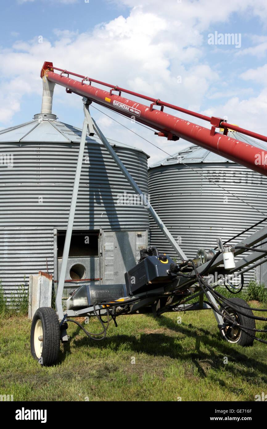 A Sakundiak grain auger moving grain into a storage bin on a