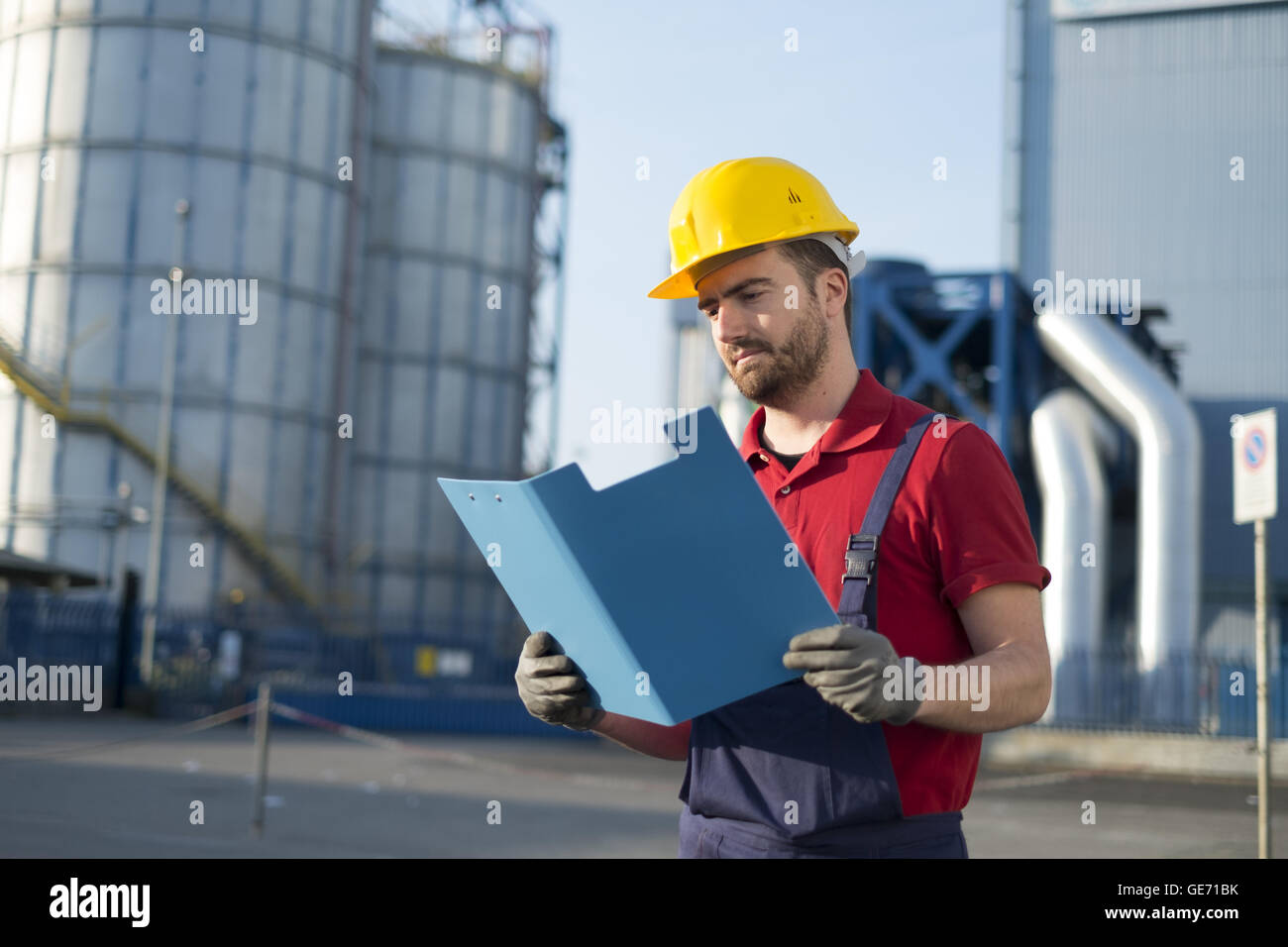 laborer outside a factory working dressed with safety overalls equipment - Stock Image