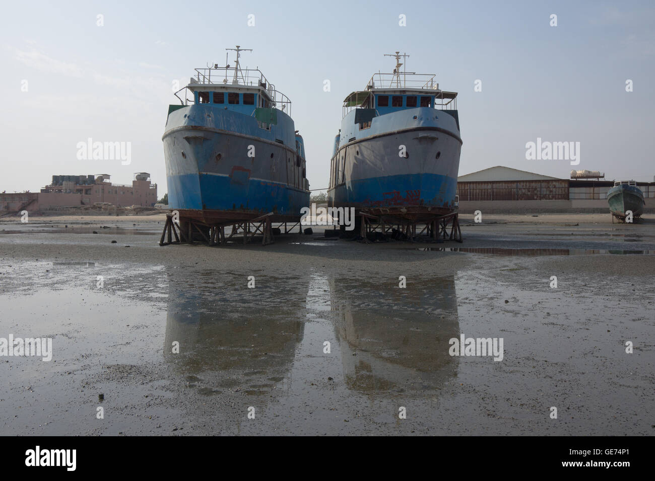 Two boats in dry dock on stands. - Stock Image