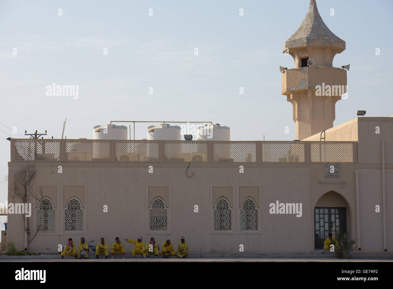 Migrant workers cleaning in Kuwait take a refuge in the shade of a Mosque from the hot weather - Stock Image