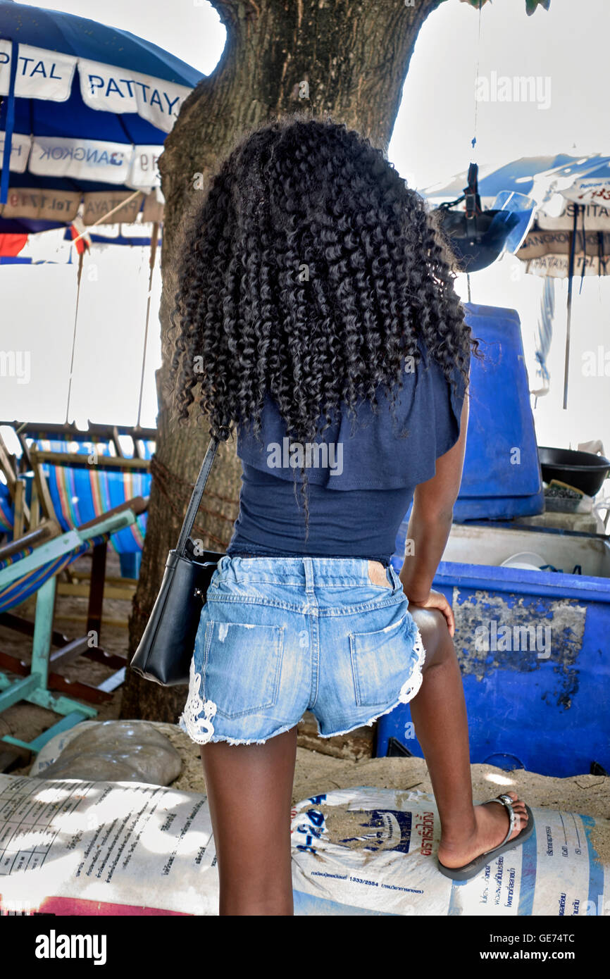 Young teenage black girl sporting her crinkly Afro Caribbean hair style. - Stock Image
