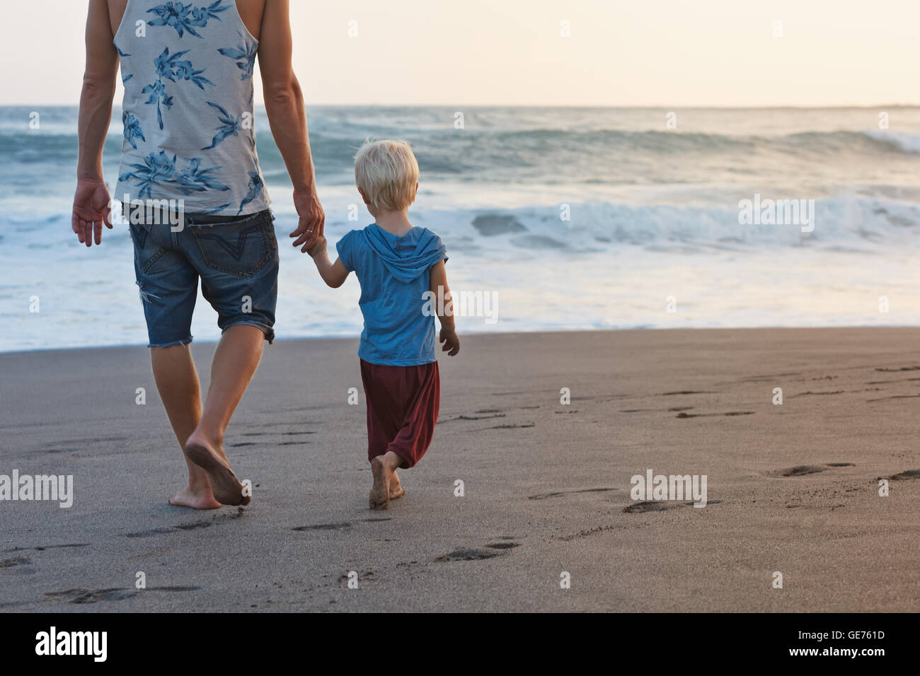 Happy family - barefoot father holds baby son hand, walk with fun along sunset sea surf on black sand beach. Travel - Stock Image