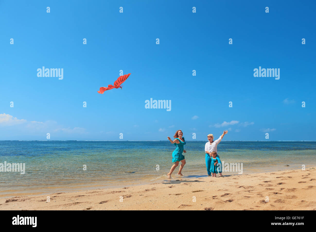 Happy family on beach - grandmother, mother, baby girl have fun, woman runs along sea surf with water splashes launching - Stock Image