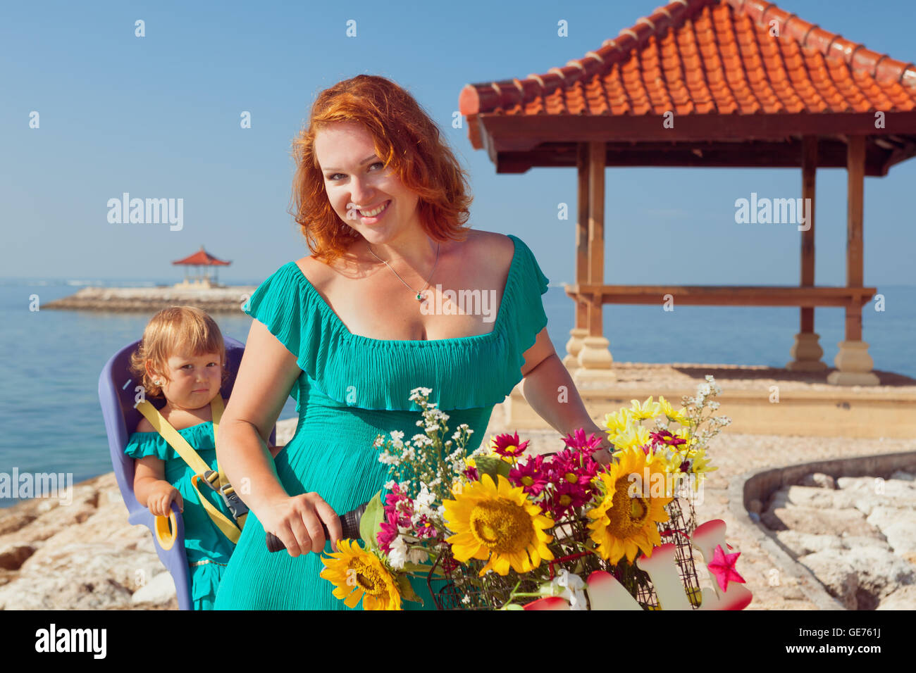Happy family - mother bicycling and have fun with little daughter in baby bike seat on sea beach. Active parents, - Stock Image