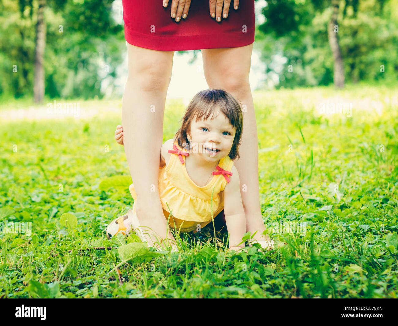 one-year old baby girl between mother legs outdoors - Stock Image