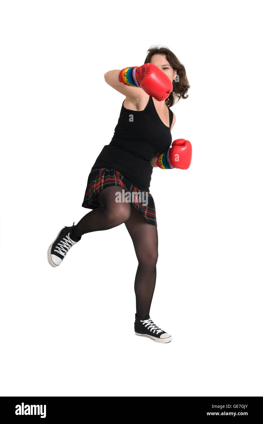 young woman with boxing gloves throws a punch - Stock Image