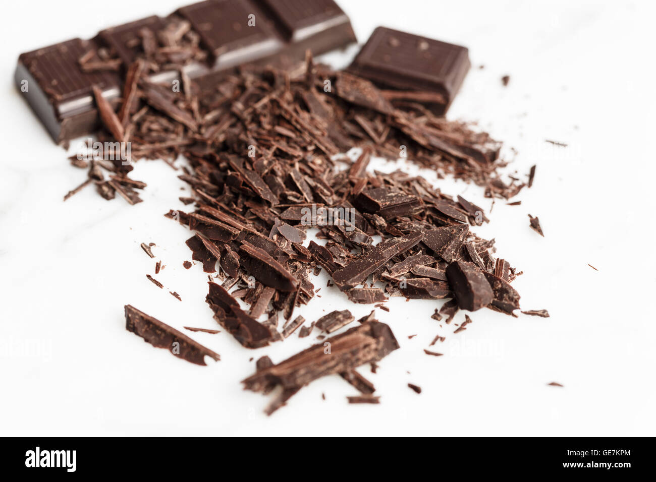 chocolate bar and shavings on white background - Stock Image