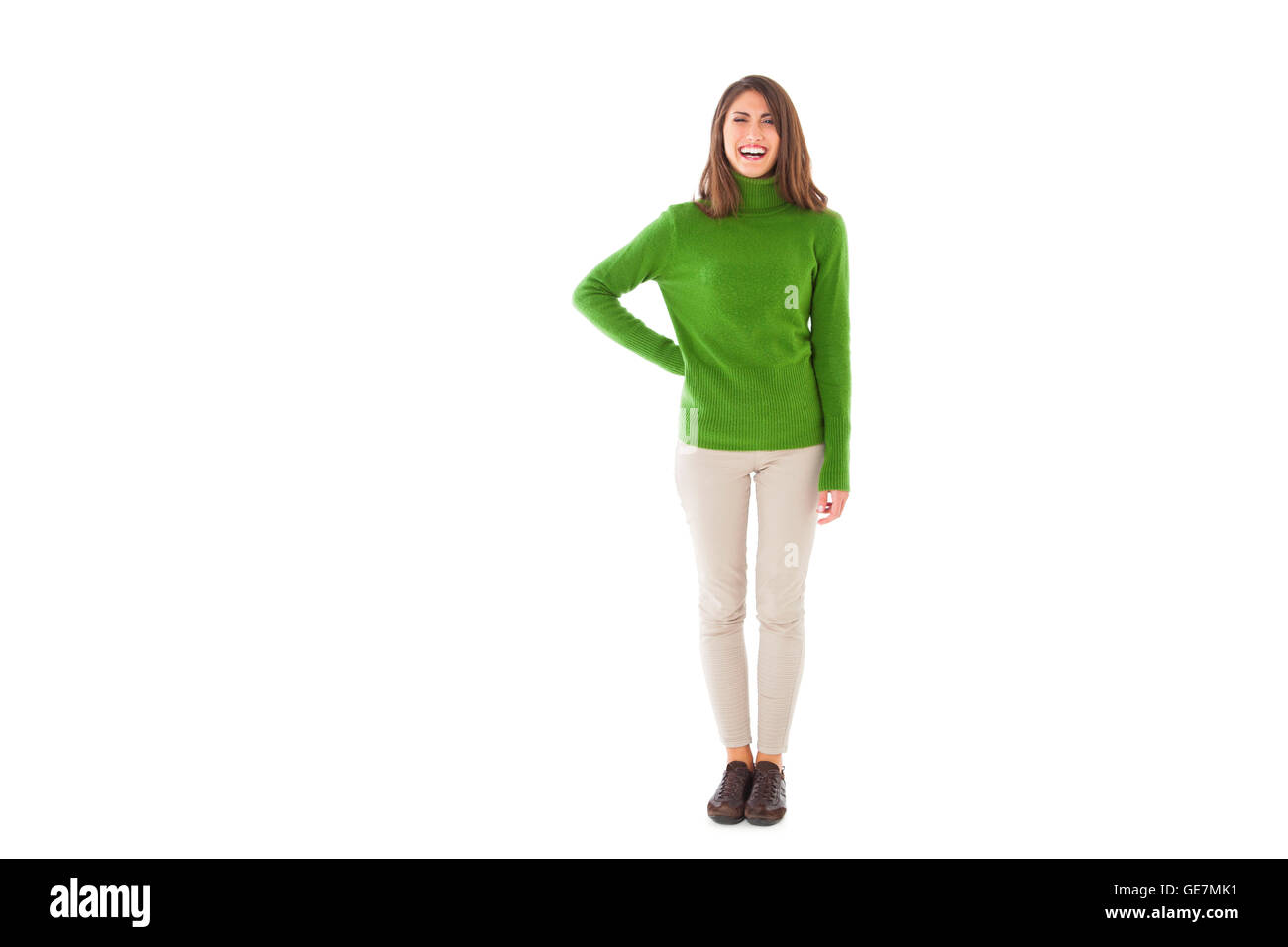 Full length of young woman smiling. Beautiful female is wearing green turtleneck sweater. She is standing isolated Stock Photo