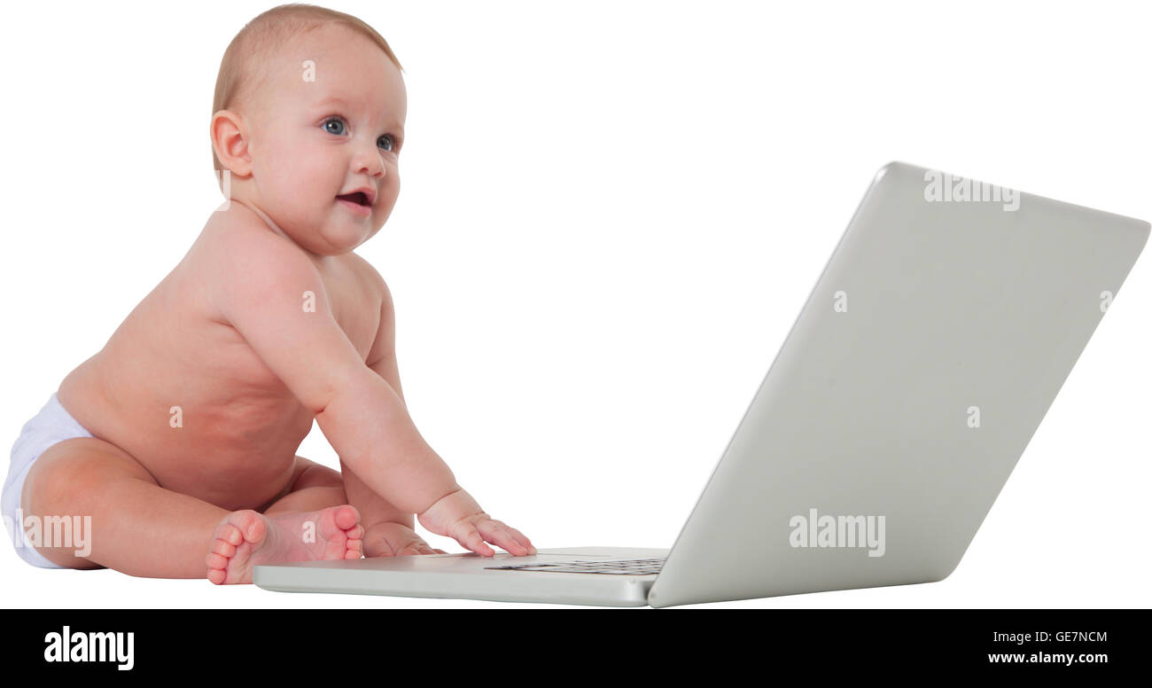 A photo of cute baby boy using laptop computer Full length of toddler is with wireless technology He is sitting - Stock Image