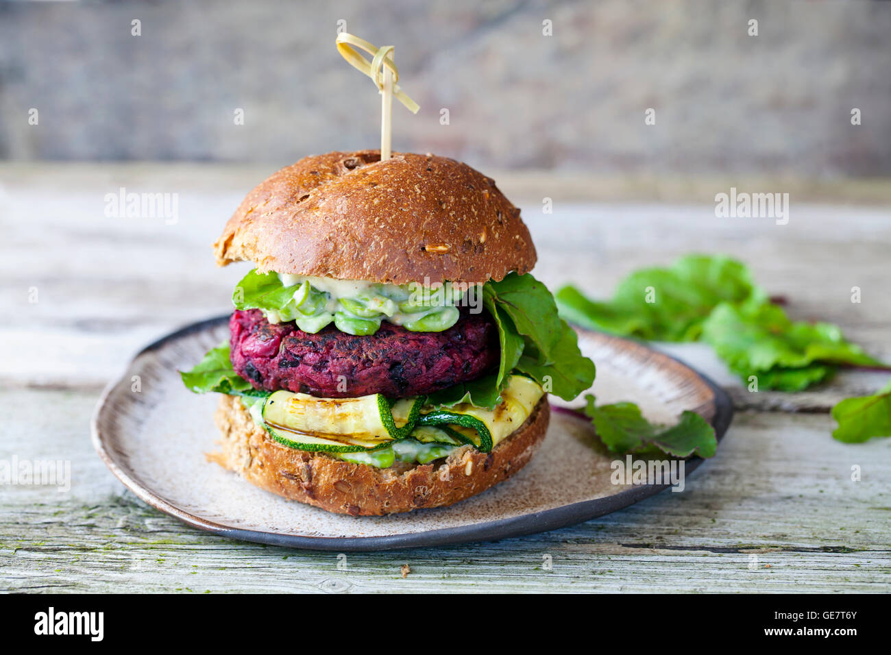 Vegetarian beetroot and black beans burger with grilled courgettes and broad beans - Stock Image