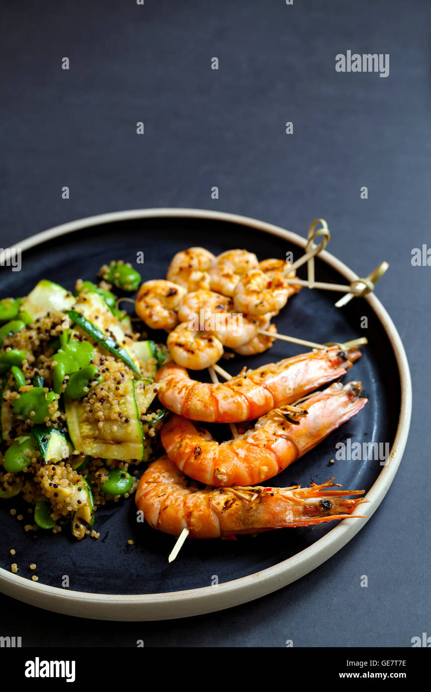 Grilled tiger prawns with quinoa, courgettes and broad bean salad - Stock Image