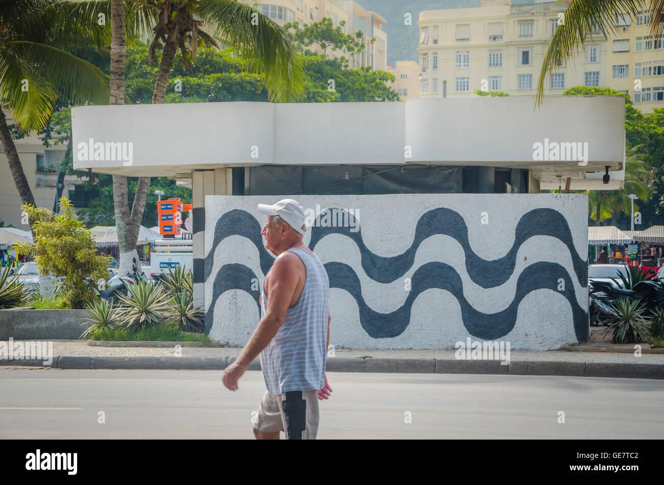 RIO DE JANEIRO, BRAZIL - MARCH 06, 2016: Man walking into wall with sidewalk mosaic of Copacabana Beach, Rio De Stock Photo
