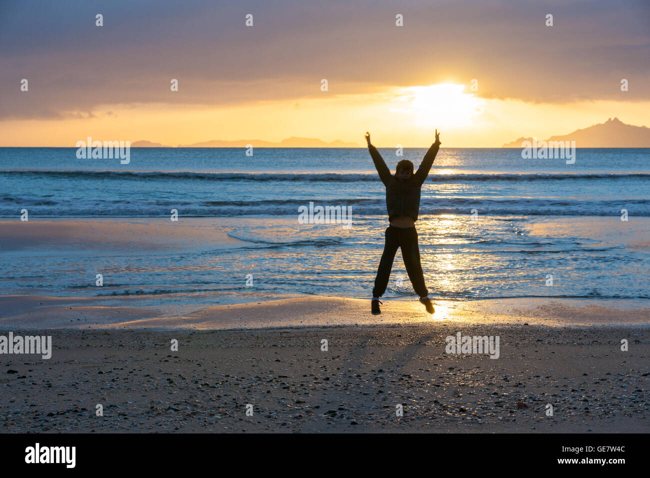 Sunrise glistens over water from horizon and off-shore islands as boy jumps with happiness on wintry morning at - Stock Image