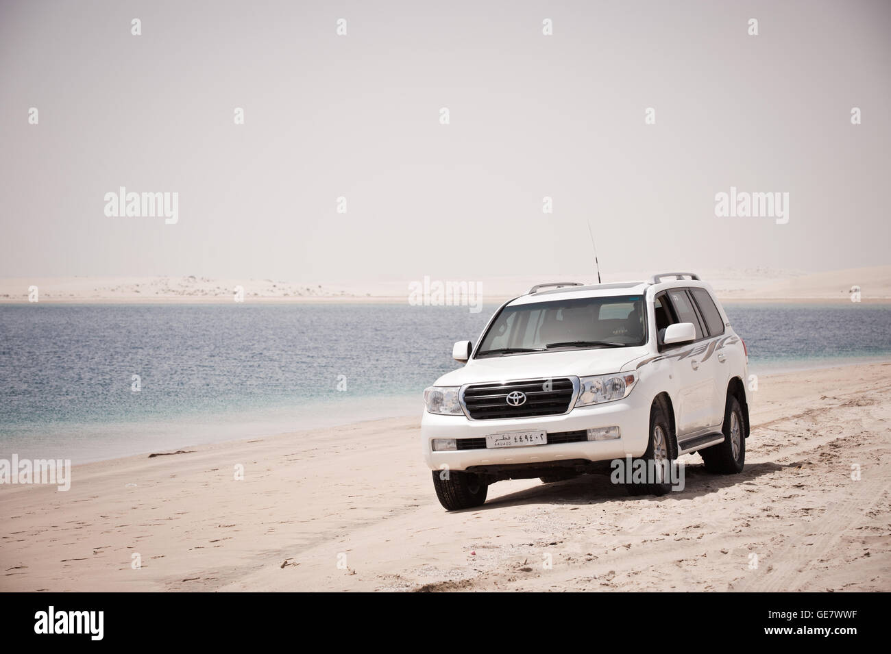 A car parked on the banks of the Inland Sea, which is an inlet of the Arabian Gulf forming a tidal lake. The Inland - Stock Image