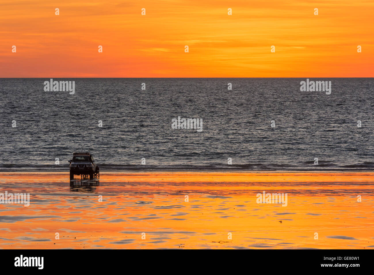 A four wheel drive vehicle parked on Cable Beach at sunset, Broome, Kimberley, Western Australia, Australia - Stock Image