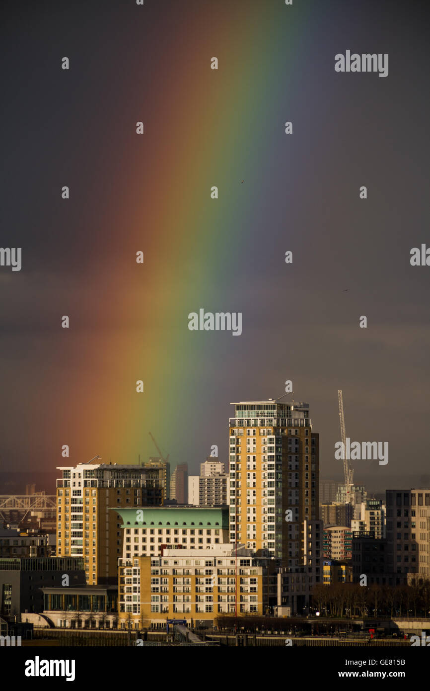 A colourful rainbow briefly breaks over some riverside apartments in south east London, UK. - Stock Image