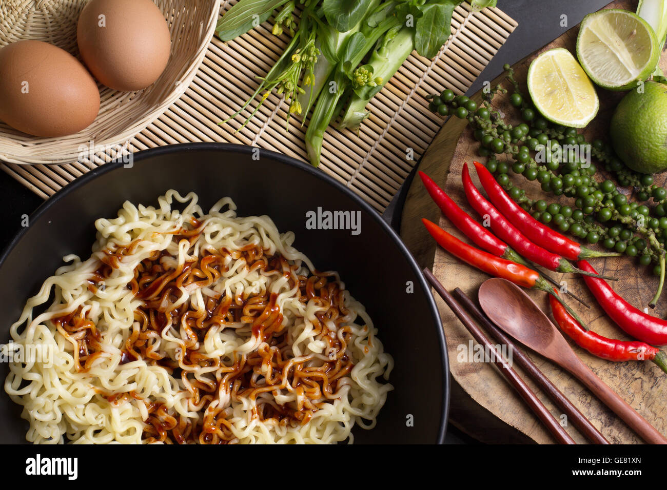 noodles in black bowl garnished on kitchen table - Stock Image