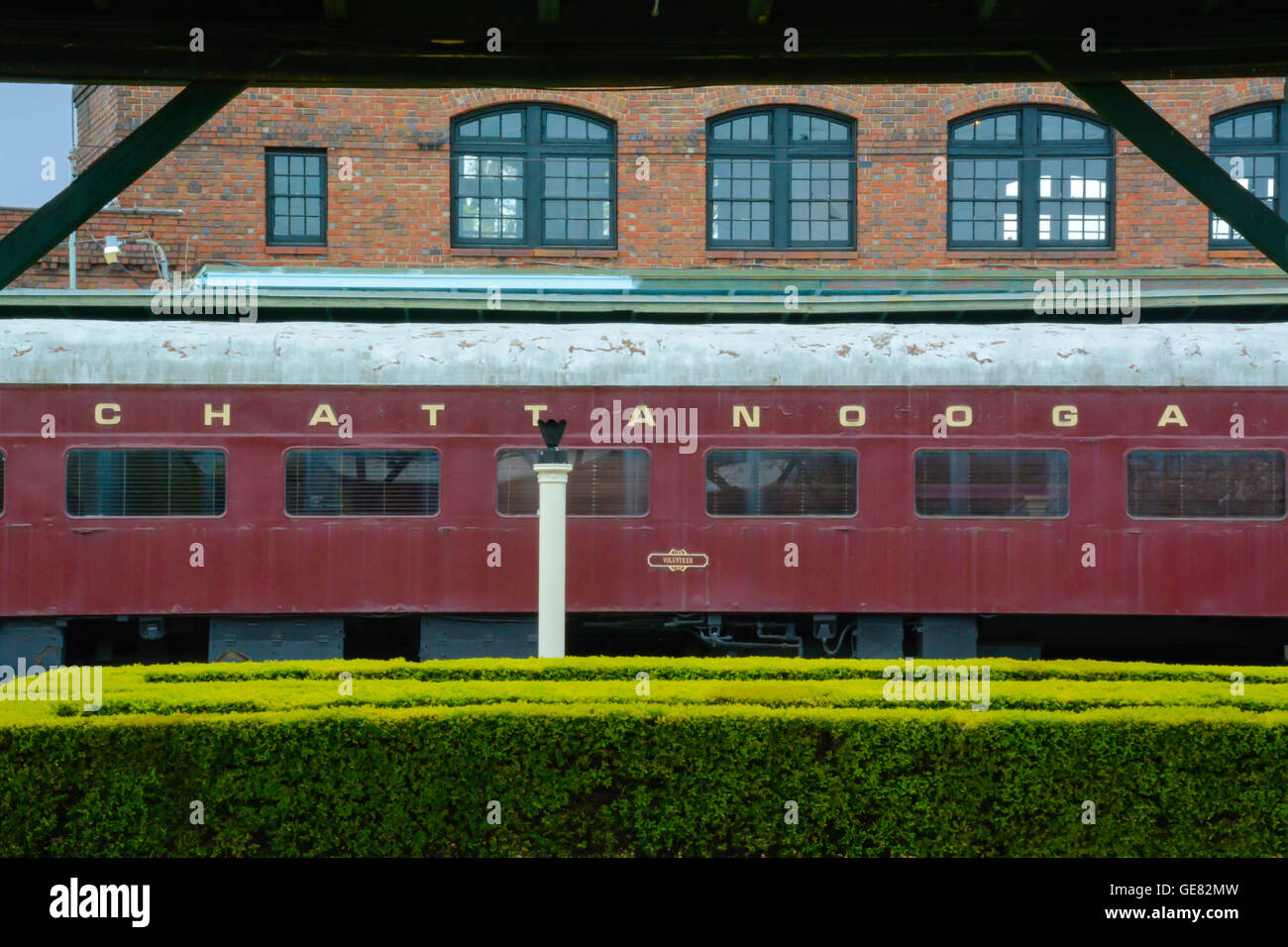 The historical Chattanooga Choo Choo Hotel's vintage branded passenger train car on tracks along side the garden - Stock Image