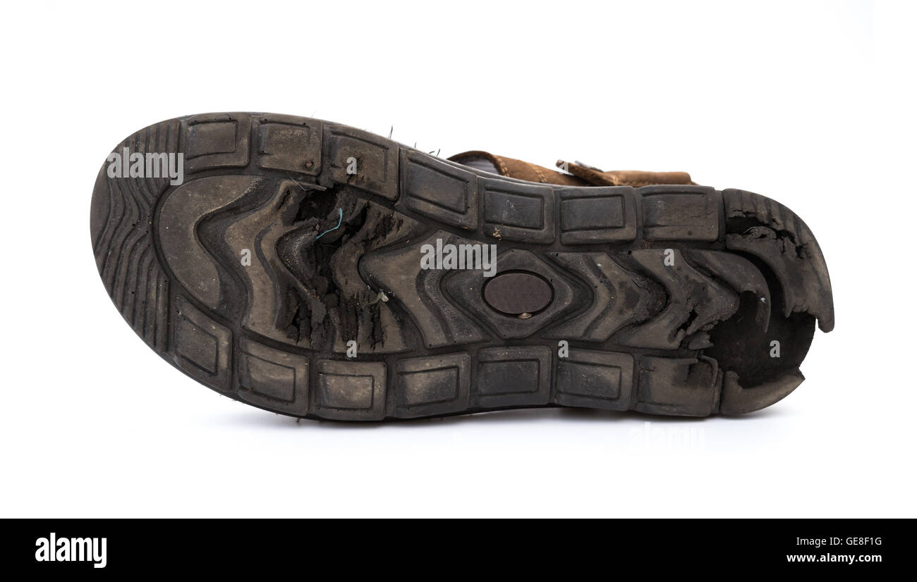 bottom of a badly worn out sandal on white - Stock Image
