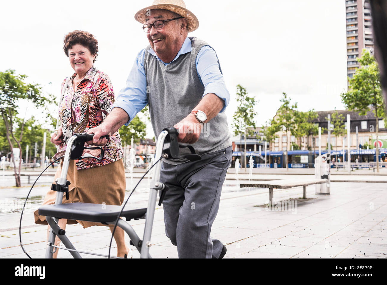 Senior man using wheeled walker for running away from his wife - Stock Image