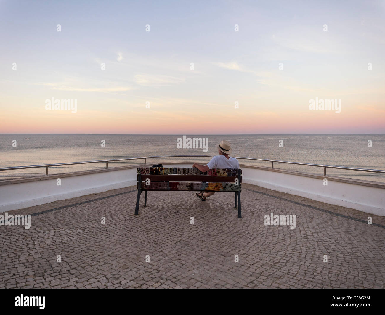 Portugal, Senior man siting on bench watching sunrise - Stock Image