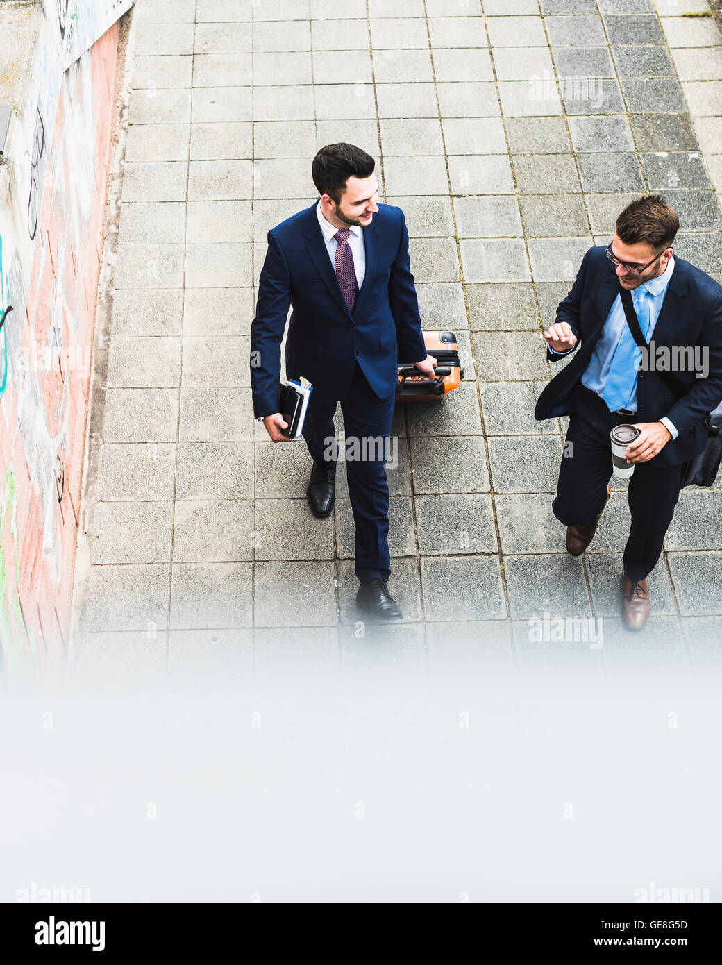 Businessmen on business trip walking with wheeled luggage - Stock Image