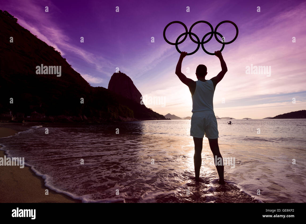 RIO DE JANEIRO - APRIL 2, 2016: Silhouette of an athlete holds Olympic rings at a colorful sunrise at Sugarloaf - Stock Image