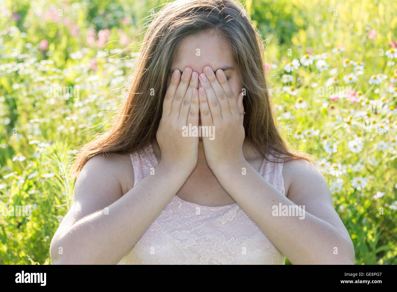 Sad girl covers face with her hands and weeps - Stock Image