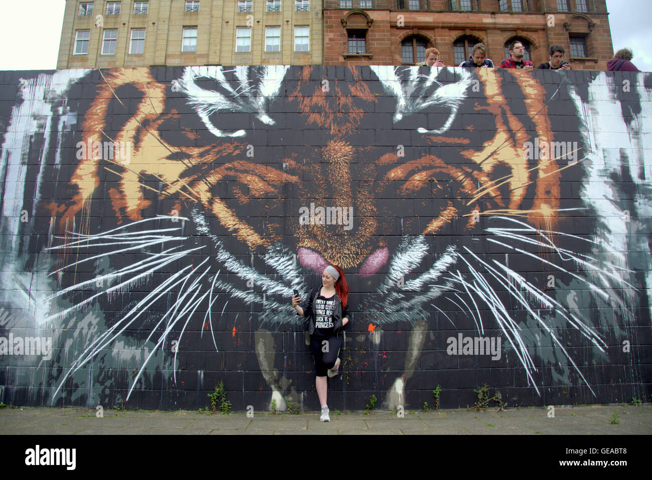 Glasgow, Scotland, UK 23rd July 2016. The Tiger mural on the River Clyde finds itself at the centre of the Pokémon phenome. The artwork by local Artist Art Pistol has found itself at the centre of the city's Poke Stop Glasgow's newest social hub for gamers of all ages. Attracting a wide gamut  of people to the Riverside the strange sight of a large crowd individually contemplating their phones is proving one of the city's latest attractions. Credit:  Gerard Ferry/Alamy Live News Stock Photo