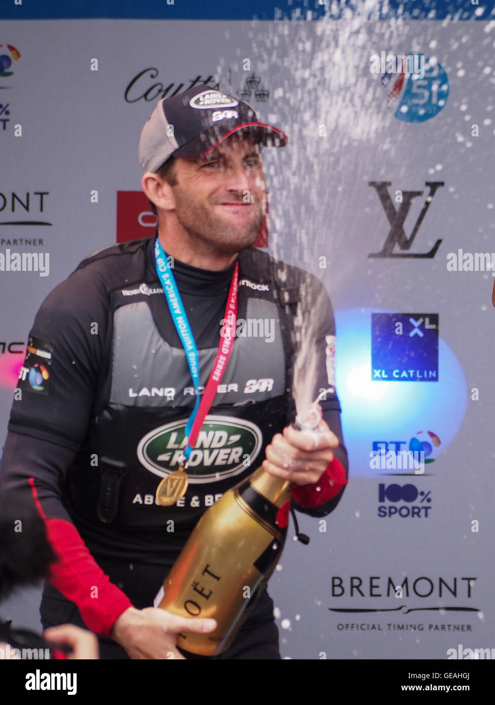 Portsmouth, UK, July 24 2016. Sir Ben Ainslie sprays champaign the podium after winning the regatta at The Americas - Stock Image