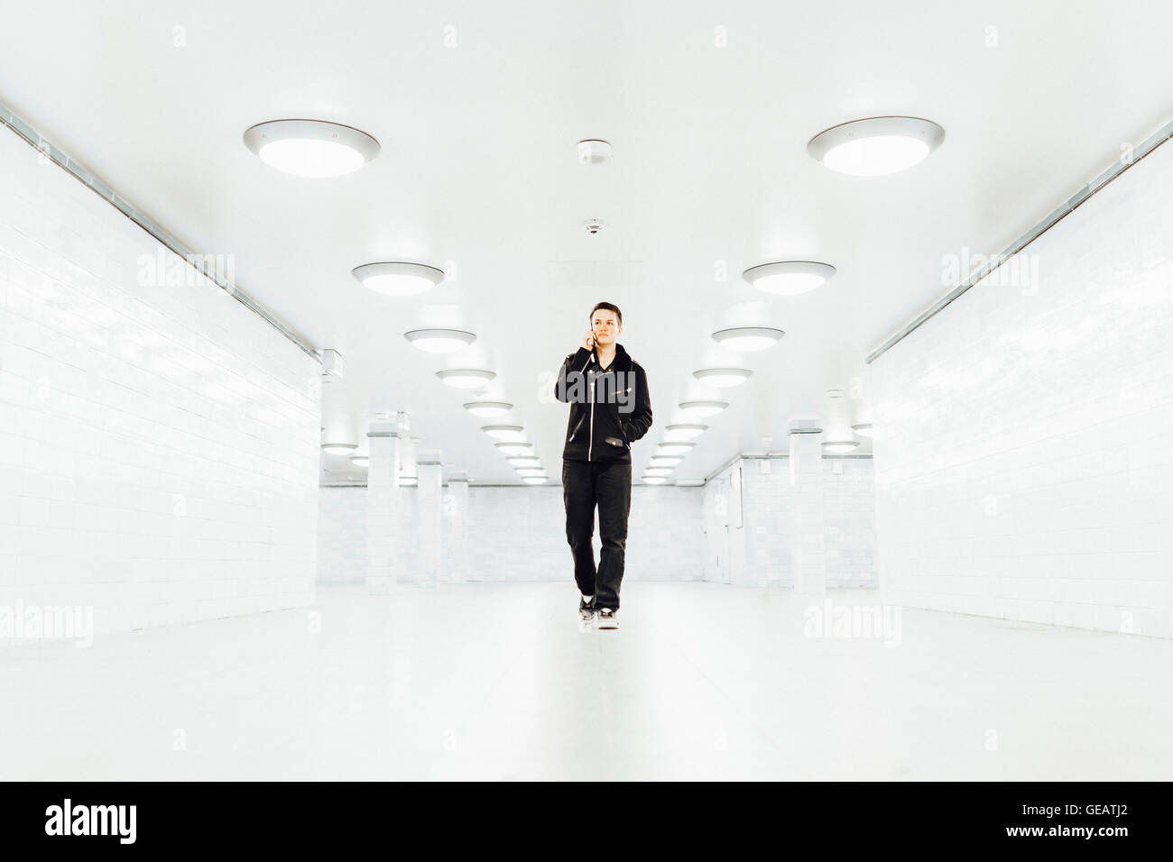 Teenager walking through an empty subway tunnel while talking on the phone in Berlin - Stock Image