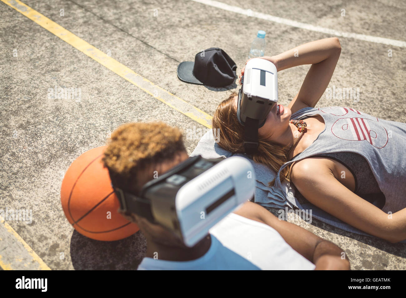 Young couple using virtual reality glasses, resting heads on basketball - Stock Image