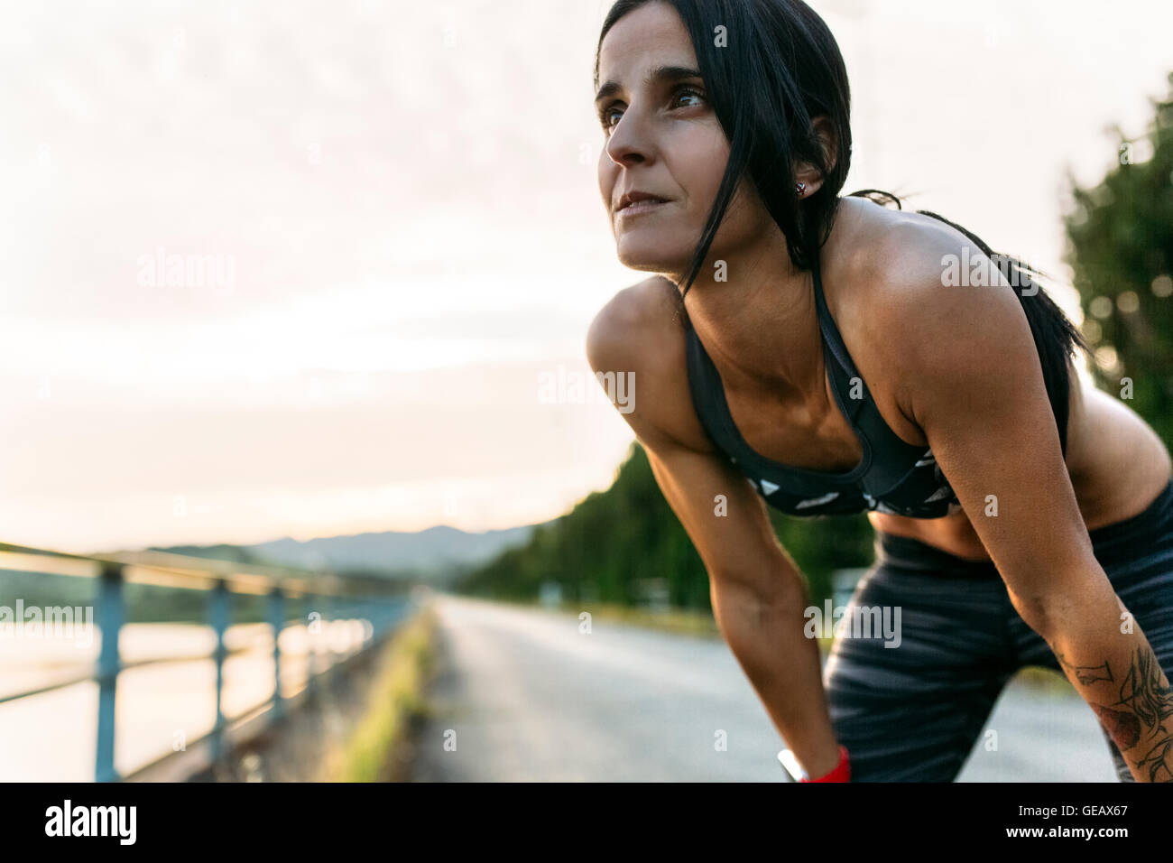 Woman taking a breather at training - Stock Image