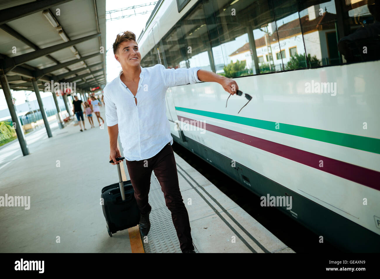 Young man at station platform running to get on the train - Stock Image