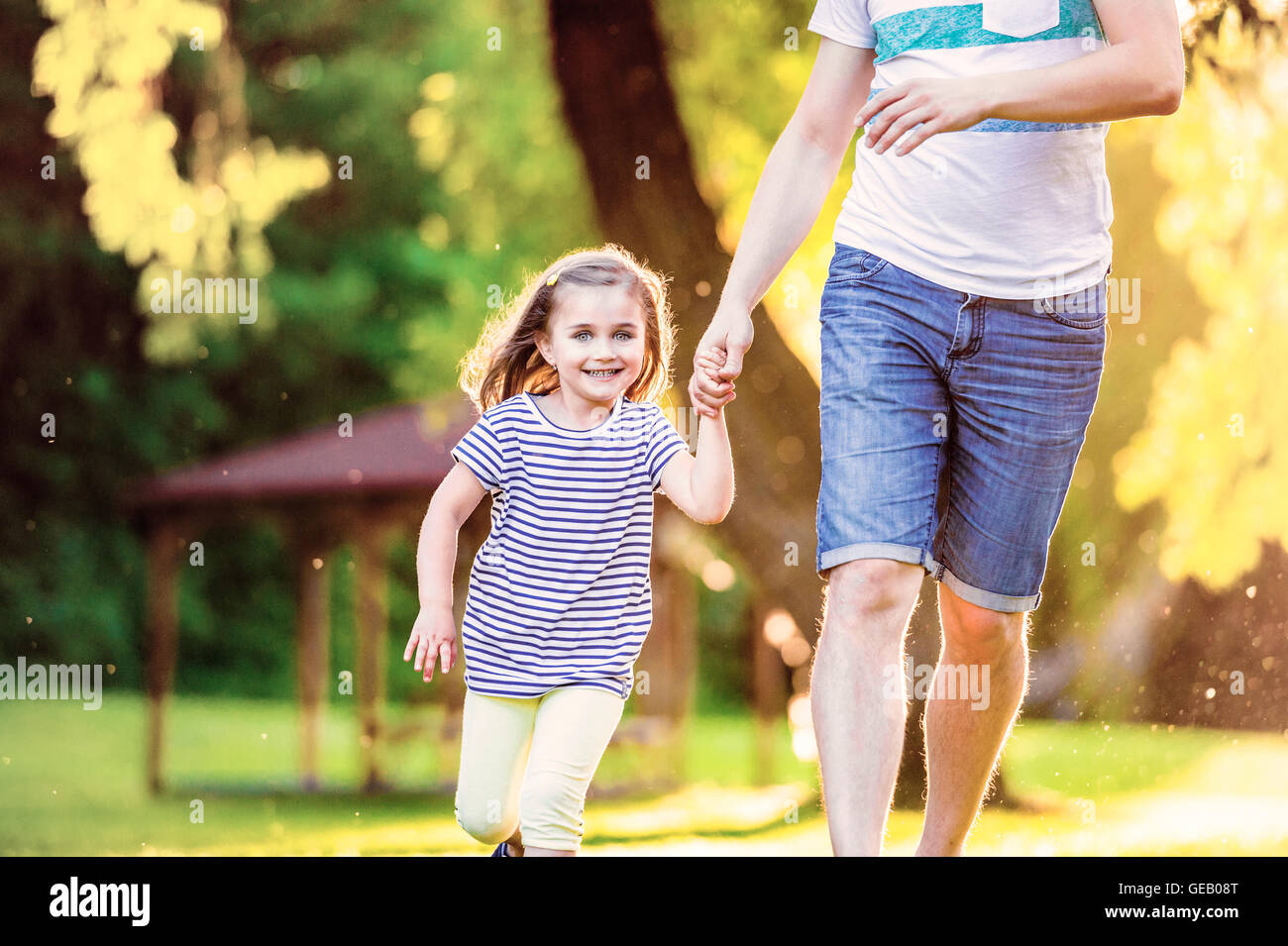 0e730e5ebf Portrait of smiling little girl running with her father hand in hand in a  park -