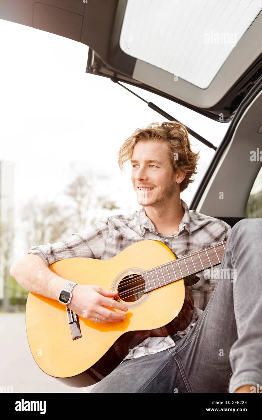 Portrait of smiling young man sitting at backside of his car playing guitar - Stock Image