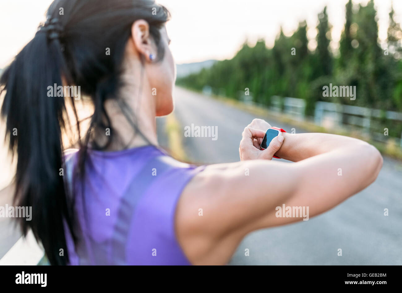 Woman adjustung settings of smart watch for outdoor training - Stock Image