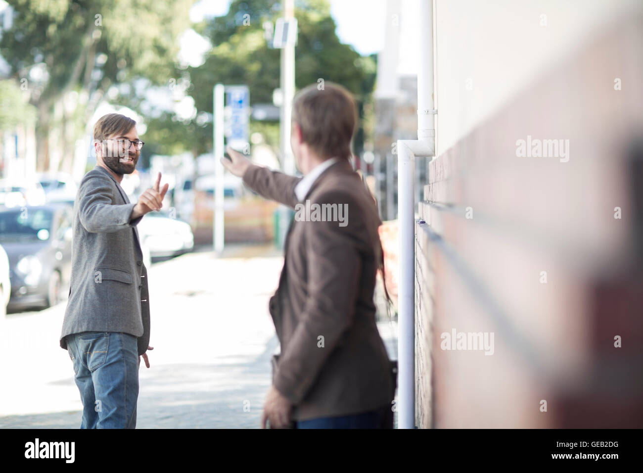 Two men saying goodbye in city - Stock Image