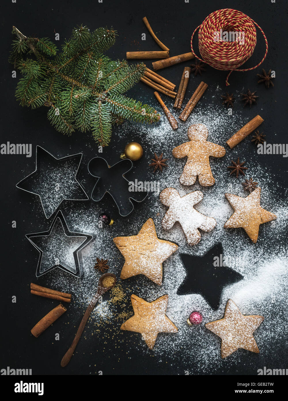 Cooked Christmas holiday traditional gingerbread cookies with sugar powder, anise and cinnamon sticks on black background - Stock Image